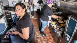 Happy cashier with payment on busy food truck