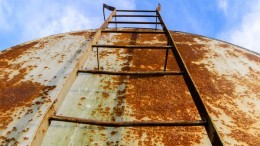 Corroded and rusty oil storage barrel stairs against beautiful blue skies.