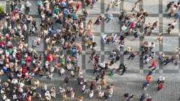 PRAGUE, CZECH REPUBLIC - SEPTEMBER 9, 2014: Large group of tourists at Prague central square looking up to Old Town Hall tower.