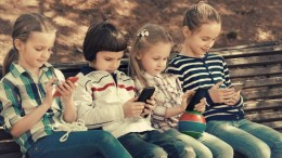 Positive kids sitting on bench with mobile devices in street