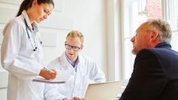 Ärzte und Patient in der Sprechstunde beraten über eine Therapie