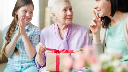 Elderly woman unwrapping package between her daughter and granddaughter