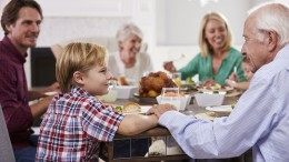 Extended Family Group Sit Around Table Eating Meal At Home