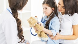 Mother and daughter at pediatrician office, girl examinate heart beat of teddy bear with stethoscope