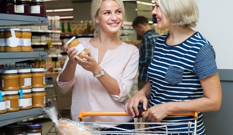 Two women of all ages are buying jam and honey  at the supermarket