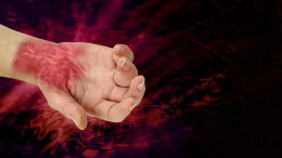 The PAIN of RSI - wrist and hand palm face up showing painful looking nasty redness across wrist area symbolizing the pain of RSI on a black and angry red wide background representing pain