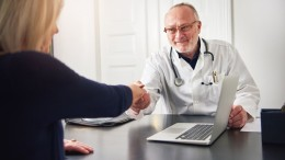 Mature doctor with stethoscope sitting at table with laptop and shaking hands while communicating with woman.
