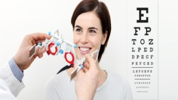 smile woman doing eyesight measurement with trial frame and visual test chart on white