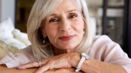 Close up portrait of relaxed older woman smiling and sitting on sofa