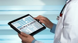 doctor consulting medical record on the tablet with text sclerosis multiple in diagnostic / Neurologist with a sclerosis multiple diagnosis in digital medical report