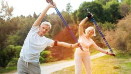 Physical activity. Joyful nice active people standing in the part and holding Nordic walking poles while doing physical exercises