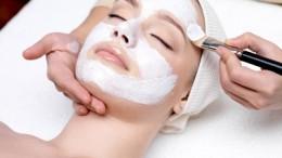 Beautiful young woman receiving facial mask at beauty salon - indoors