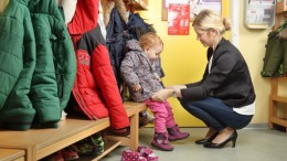 Mutter holt Kind von Kinderkirppe ab_ 2