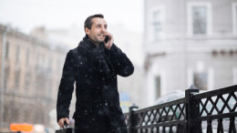 Portrait of handsome bearded entrepreneur with briefcase walking around winter city while talking to his colleague on smartphone, blurred background