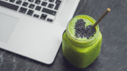 Fresh green smoothie with banana and spinach with heart of sesame seeds and a laptop Love for a healthy raw food concept.