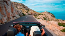 Couple in Sunny Cars convertible on road to Cap de Formentor peninsula, Mallorca, Balearic Islands, Spain