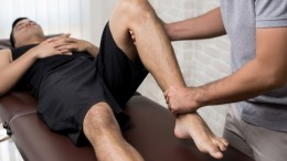 Therapist treating injured leg of athlete male patient in clinic - sport physical therapy concept