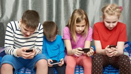 Children playing game on mobile phones at home