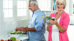 Portrait of smiling senior woman holding colander with man preparing vegetables in kitchen