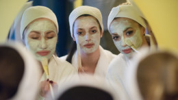 group of female friends in spa have fun, celebrate bachelorette party, puting face mask and looking in mirror