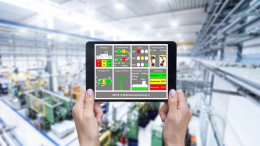Horizontal color image of female hands holding white screen digital tablet in a modern plastic production line. Ordering on-line from injection moulding factory on a touchscreen tablet computer. Large factory, industrial machines, robots and manufacturing equipment arranged on clean and shiny flooring in background.