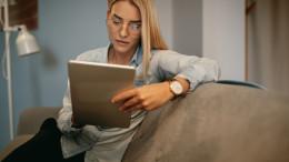 Frau sitzt auf der Couch mit ihrem Tablet in der Hand