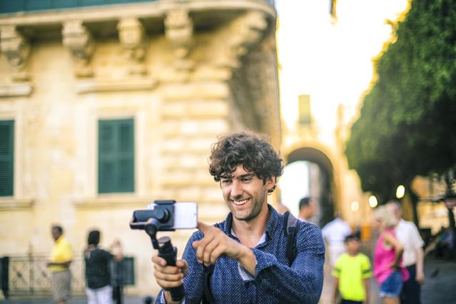 Mann mit Selfie-Stick vor Gebäude