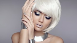 Glitter makeup. Bob hair. Beauty Portrait of blond model with short shiny hairstyle. Silver jewelry set. Concept Coloring Hair.