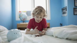 Kind liegt auf dem Bett und zählt die Münzen aus seinem Sparschwein