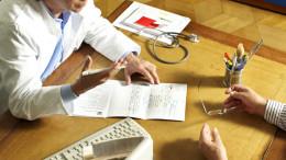 Arzt unterhält sich mit Patiention am Tisch mit Dokumenten