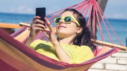Frau liegt in einer Hängematte am Meer mit einem Handy in der Hand