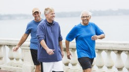 Three multi-ethnic mature men getting their exercising, power walking in a park on the waterfront.  The senior man wearing eyeglasses is Hispanic, in his late 70s.  His friends are in their 50s.