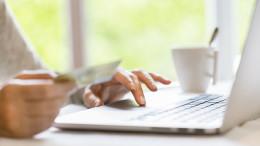 Eine Frau tippt Ihre Kreditkarteninformationen ein, um etwas online zu bestellen