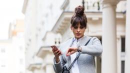 Frau mit Handy schaut auf Uhr