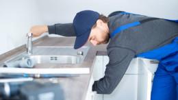 Installateur im Blaumann arbeitet an einem Waschbecken