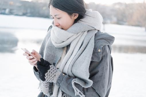 Frau mit Handy im Winter