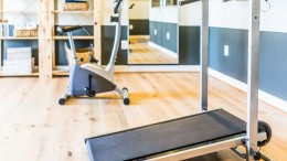 Home gym with treadmill, mirror and bicycle machine with sunlight coming through window in home, apartment or house