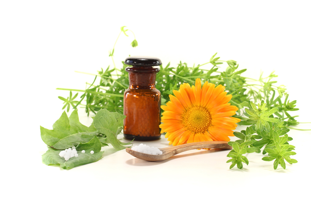 Homöopathie mit Globuli, einer Apothekerflasche sowie Naturheilkräutern und Ringelblume