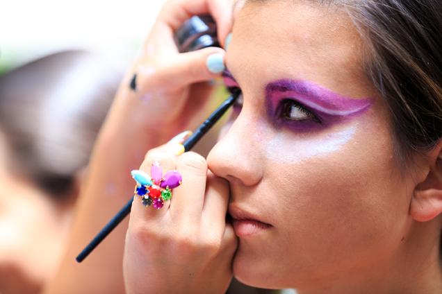 Mädchen wird bunt an den Augen für Karneval geschminkt