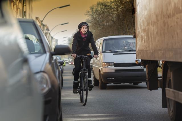 Frau faehrt auf einer stark befahrenen Straße Fahrrad
