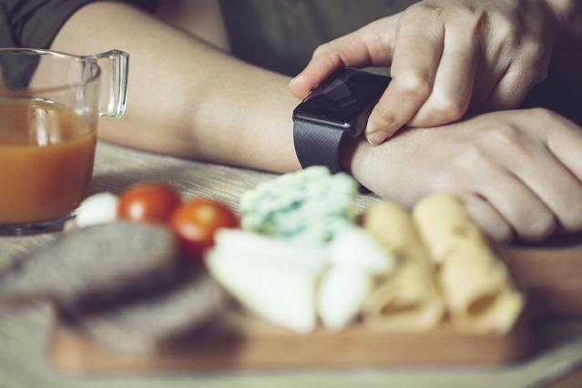 Person schaut auf seine Smartwatch, während sie zu Abend isst.