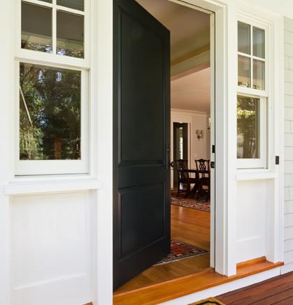 """Eine offene Hauseingangstuer, davor eine Fußmatte mit der Aufschrift """"Welcome"""" und ein Einblick in das Hausinnere."""