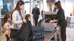Frau mit Kindern gehen am Flughafen durch eine Sicherheitskontrolle.