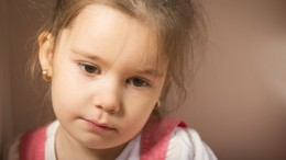 Expressive little girl, melancholic, thinking away, studio shot on brown background