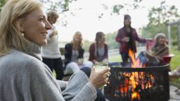 Lachende Frau mit Glas vor Osterfeuer - D.A.S. Verbraucherfrage