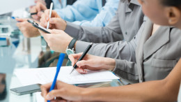 Close-up Of A Business People Hands Writing Note During Meeting