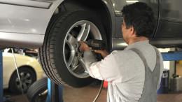 Mann befindet sich in einer Werkstatt und wechselt einen Reifen.