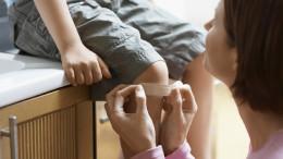 Mutter klebt ihrem Sohn ein Pflaster auf das Knie