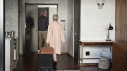 Paar verlaesst ihre Wohnung, um in den Urlaub zu fahren