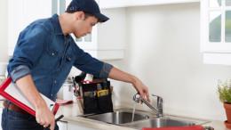 Ein Handwerker repariert einen Wasserhahn.